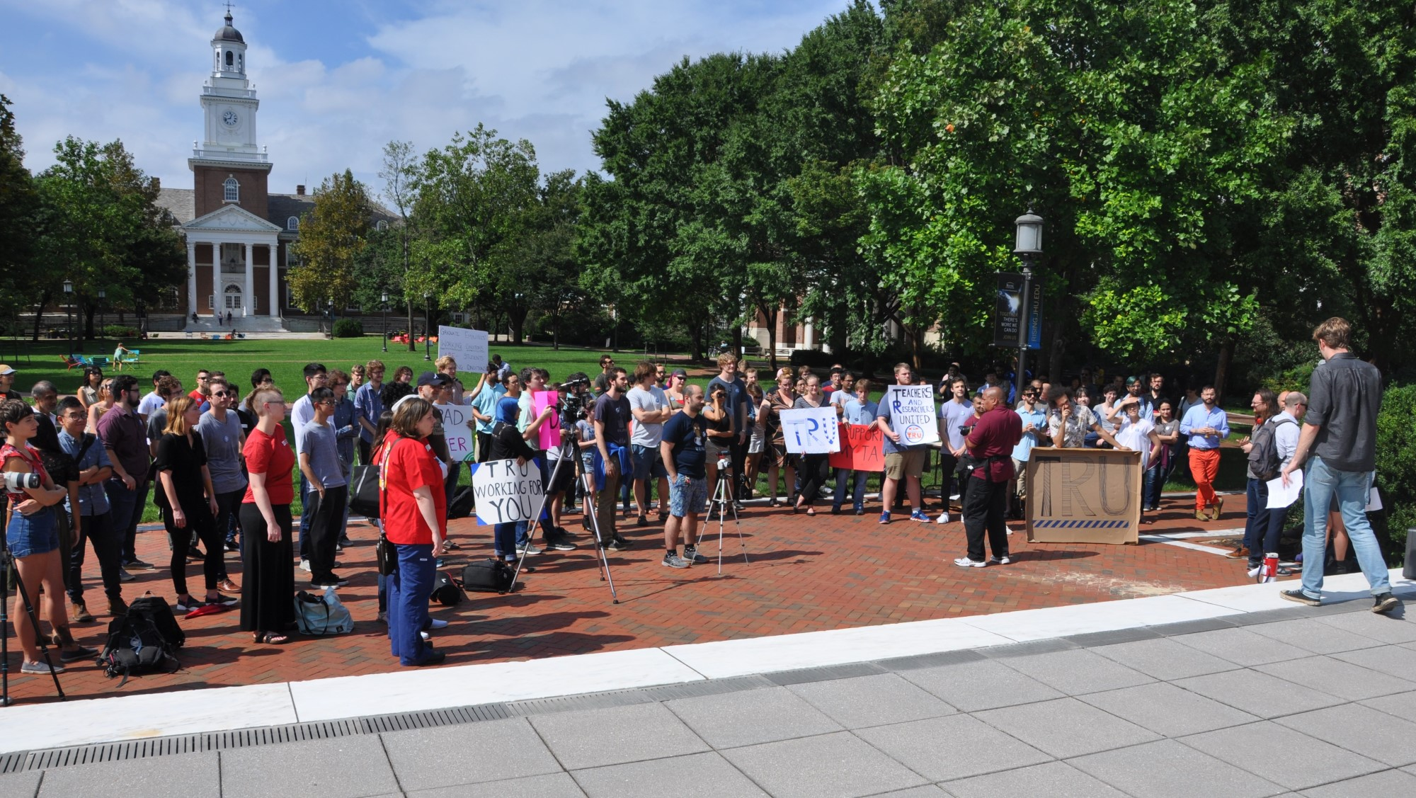 "A crowd gathers in front of the Eisenhower library steps under a cloudless blue sky. Some people carry signs saying ""I support my TA"" or ""TRU working for you"" or ""Grad worker"". Many people are also wearing buttons. There is a photographer and two videographers. Gilman hall is visible in the background."