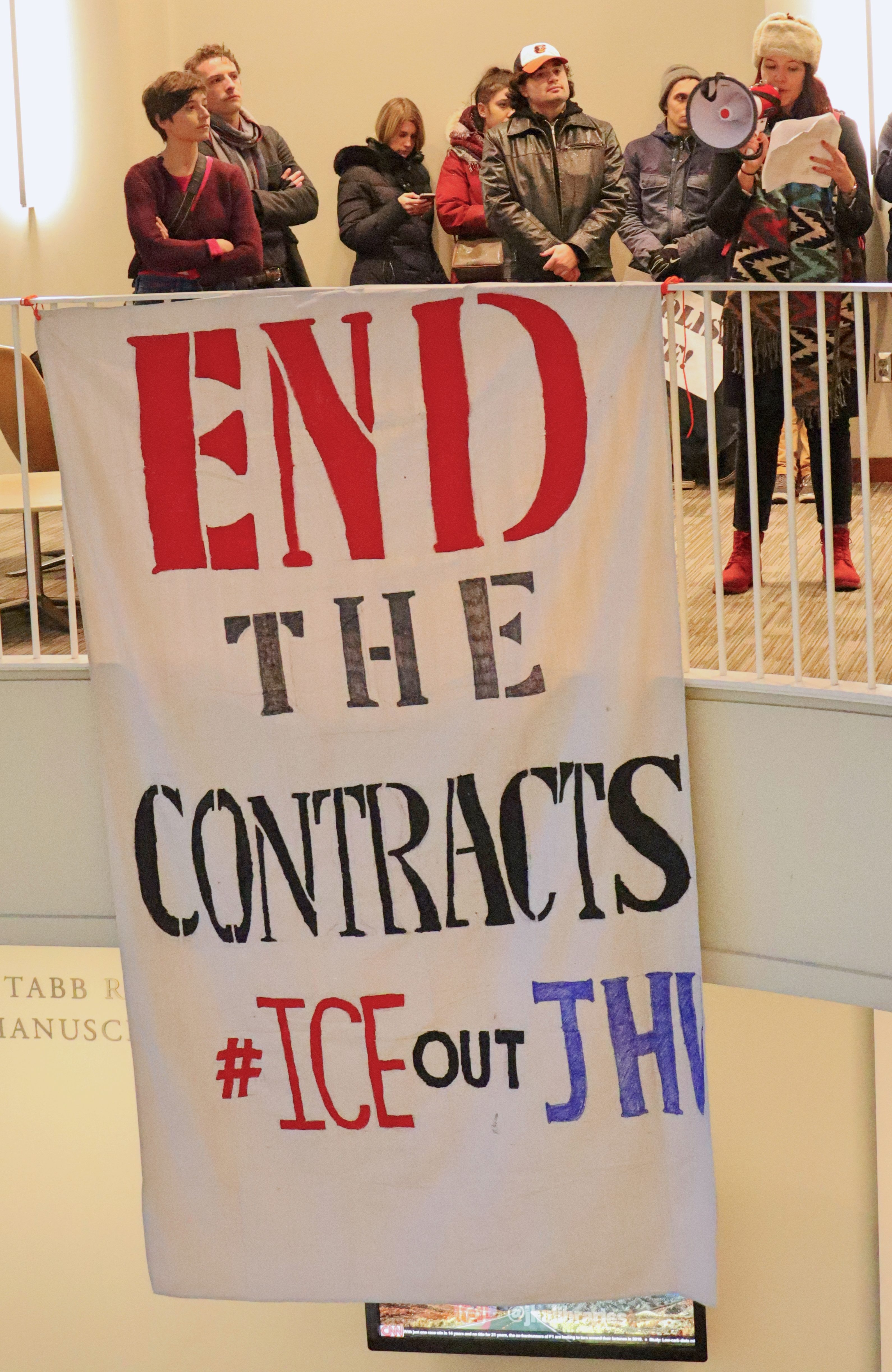 "A group of people stand on the upper level balcony of Brody as in front of them a large banner hangs down off the railing proclaiming ""END THE CONTRACTS #ICEoutjhu"""