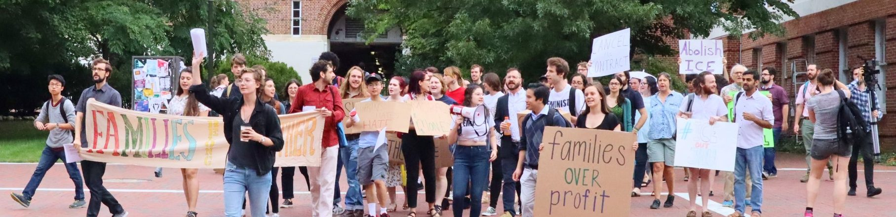 A large group of people carrying signs marches from Gilman Hall towards Garland