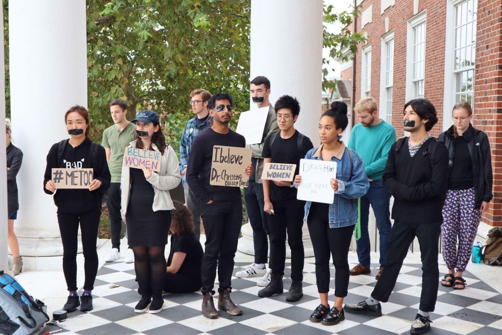 "A group of people, dressed predominantly in black, stands under the columned porch of Gilman hall. Some individuals have black tape over their mouths, while others hold signs saying things like ""#MeToo"" or ""Believe Women"""