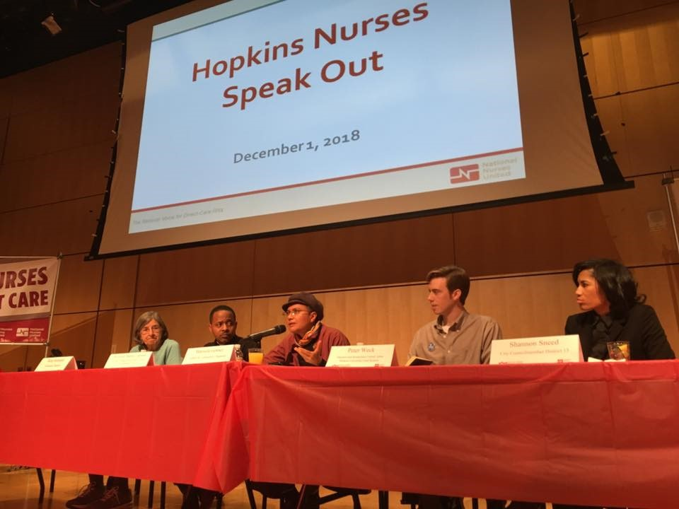 "five people st in a row at a long red table. A sign in front of each person identifies them. Above the panelists is a powerpoint projection reading ""Hopkins Nurses Speak Out. December 1, 2018."""