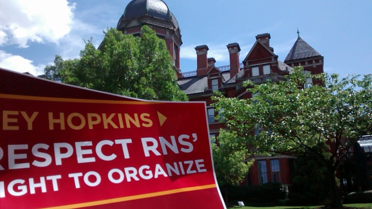 "In the foreground is a red sign which says: ""Hey Hopkins, Respect RNs' right to organize."" In the background is the facade of the Hopkins Medicine's Billing's administration building."