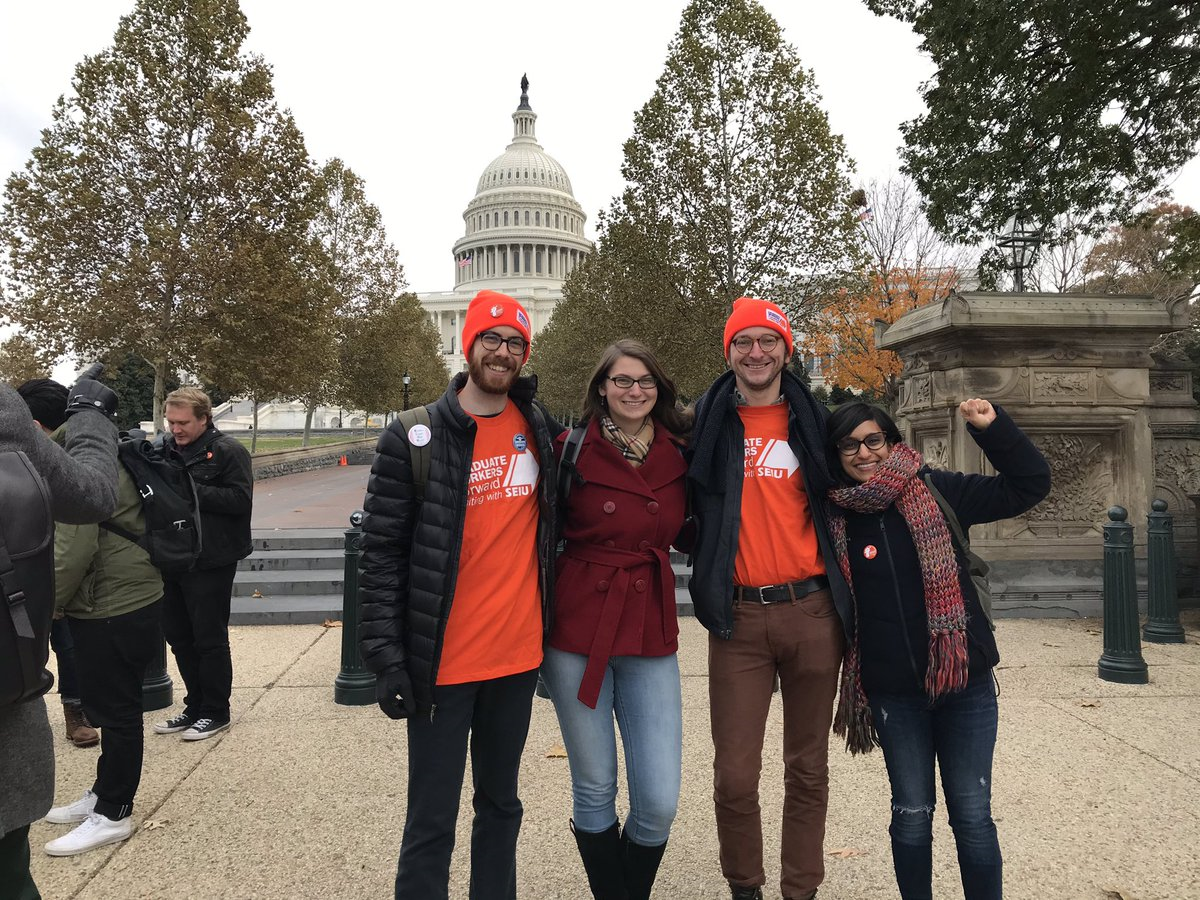 Four members of TRU stand with their arms on each other's shoulders with the Capitol building in the background. Two members are wearing orange shirts and hats with the logo for SEIU Graduate Workers Foward